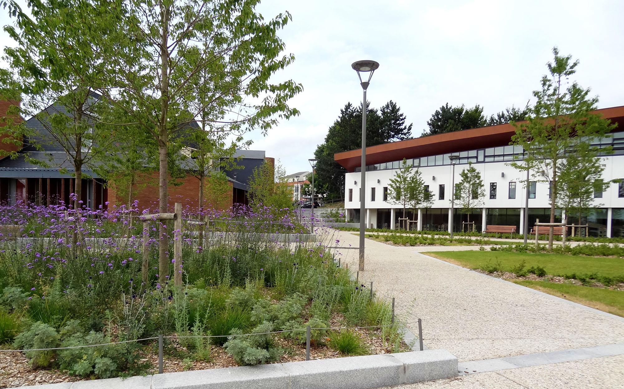 Vue sur la place jardin prenant place entre la médiathèque à droite et la mairie, à gauche